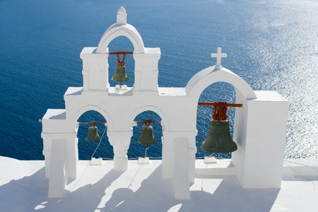 cyclades: View on calm sea surface through traditional Greek white church arch with cross and bells in village Oia of Cyclades Island Santorini Greece