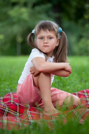 sitting area: Portrait of little militant blond girl preschooler with ponytails sitting in closed pose on the red plaid on green grass in summer