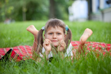 lying on grass: Portrait of little cute blond girl preschooler with ponytails who is lying on red plaid in park with green grass summer
