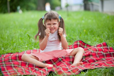 little girl sitting: Little angry cute blond girl preschooler with ponytails sitting on the red plaid on green grass in summer