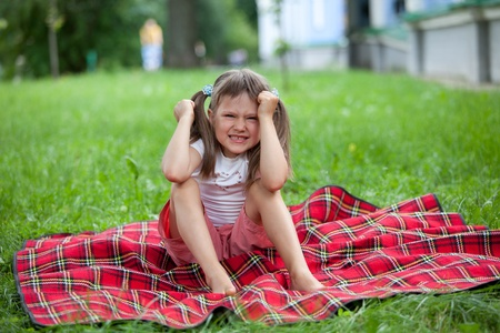 ponytails: Little angry cute blond girl preschooler with ponytails sitting on the red plaid on green grass in summer