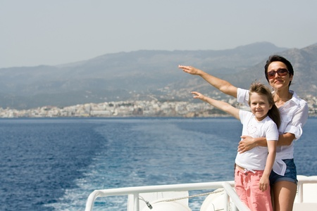 Mother, little child enjoy fresh summer wind and mountain seascape sailing by sea boat photo