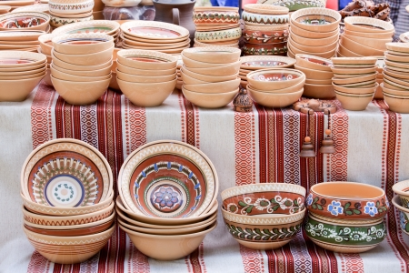 Rustic handmade ceramic clay brown pots souvenirs decorated by traditional ornament, pattern on embroidered Ukrainian towel at street handicraft market photo