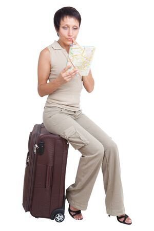 Thinking young tourist haircut woman looking at city map dressed buff trouser suit sits on the brown traveling suitcase isolated photo