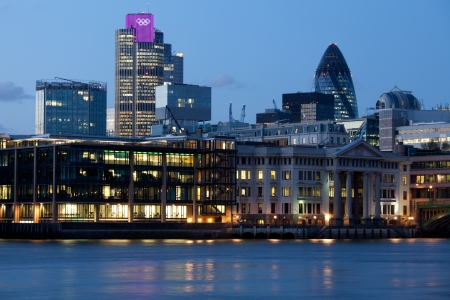 London, UK - July 1, 2012: London City, leading center of global finance on Thames river bank. View on Tower 42 Gherkin, illuminated with Olympic rings, Willis Building, Stock Exchange Tower and Lloyd`s