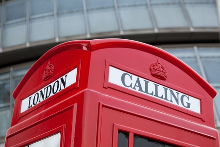 Traditional London symbol red public phone box for calling on the modern business center facade background  photo