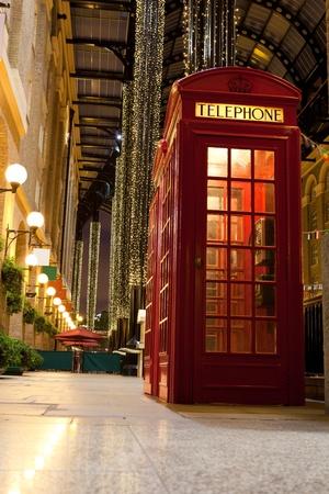 cabina telefono: Londres símbolo rojo cabina telefónica en el pasaje comercial festivamente illumibated