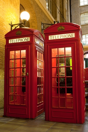 Traditional London symbol red public phone boxes at illuminated evening street  Great Britain photo