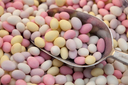 Multicolored egg-shaped candy sweet drops on metal scoop close-up in retail store photo