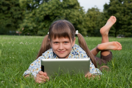 schoolgirls: Cute smiling girl teenager holding tablet digital computer, looking at camera and relaxing on green grass in sunny park