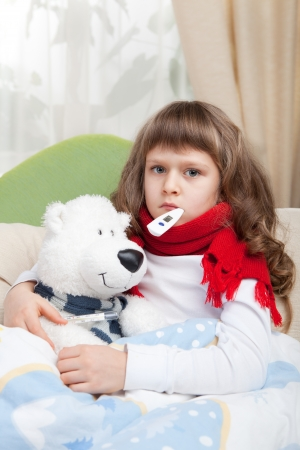 Sympathetic little sick girl with red scarf and clinical thermometer in mouth embraces white toy bear under blanket in the bed photo