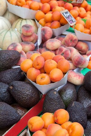 purple fig: Plates with ripe orange apricot, fig peach,  purple avocados, melons at fruit market