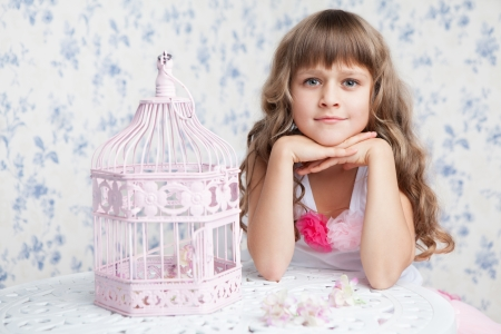 fond of children: Tender sincere dreamy romantic openhearted blond girl with long wavy hair looking at camera seating near open empty pink birdcage and lacy white table on the light blue flower background