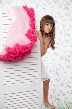 hair dressing: Young blond girl teenager with long wave hair looks out the folding screen when change of clothes Stock Photo