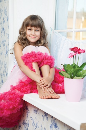 a frill: Young amazing joyful girl teenager close-up dressed luxuriant wavy skirt with frill sitting with outstretched legs on white windowsill inside room near fresh natural flower in flowerpot Stock Photo