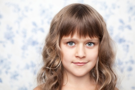 sincere: Portrait of sincere cheerful tender young blond girl child with grey eyes and wavy long hair looking at camera