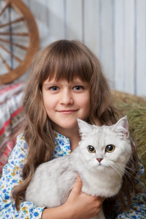 sincere: Portrait of little sincere friendly blond girl villager sitting with white cat in hands in wooden barn Stock Photo