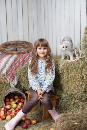 sincere girl: Portrait of sincere little blond girl villager sitting near pail with apples and white cat on hay stack in wooden hayloft