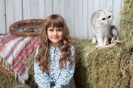 hayloft: Retrato de sincero aldeano ni�a rubia y gato blanco en la pila de heno en granero de madera