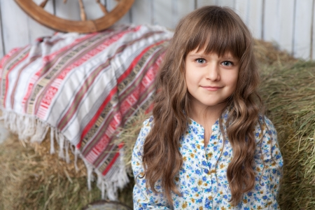 cor: Portrait of friendly little blond girl villager in wooden hayloft with vintage decoration