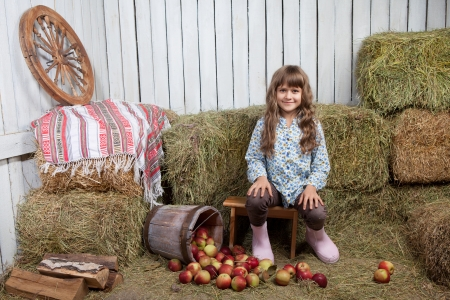 hayloft: Portrait of friendly little blond girl villager sitting on stool near inverted pail with apples in wooden vintage hayloft during harvest time