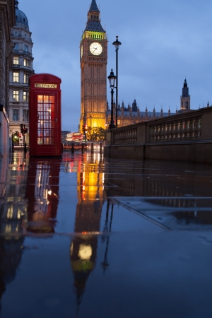 footway: Red public telephone box and illuminated clock on Big Ben tower of Westminster Palace in twilight with reflection on wet footway, Great Britain Stock Photo