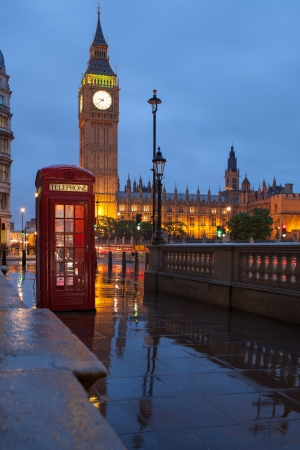 Red public telephone box and illuminated clock on Big Ben tower of Westminster Palace in twilight with reflection on wet footway, Great Britain Stock Photo