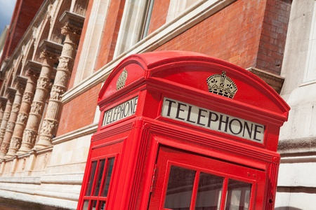Traditional London symbol red public phone box on building facade background, Great Britain photo