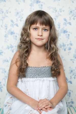Portrait of sincere cheerful tender young blond girl child with grey eyes and wavy long hair in sitting posture looking at camera photo