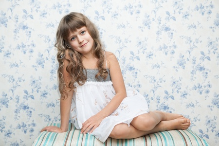 Portrait of sincere cheerful tender young blond girl child with grey eyes and wavy long hair in relaxed sitting posture looking at camera photo