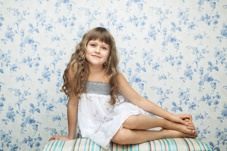 sincere: Portrait of sincere cheerful tender young blond girl child with grey eyes and wavy long hair in relaxed sitting posture looking at camera