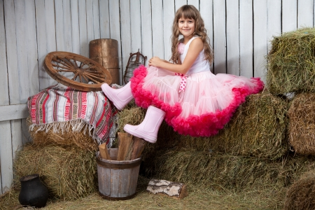Portrait of funny little blond girl villager in rubber boots dressed luxuriant wavy ball dress with frill sitting on haystack  in wooden vintage hayloft photo