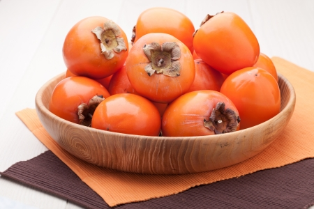 Fresh exotic tropic ripe juicy orange fruits  persimmon Diospyros served in wooden plate on table