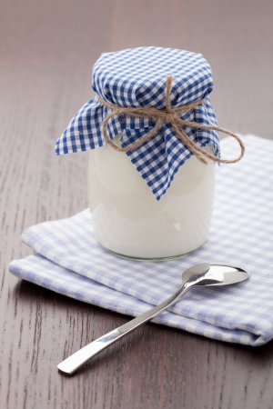 glass jar: Homemade milk yogurt in glass pot and metal spoon served on linen napkin wooden table