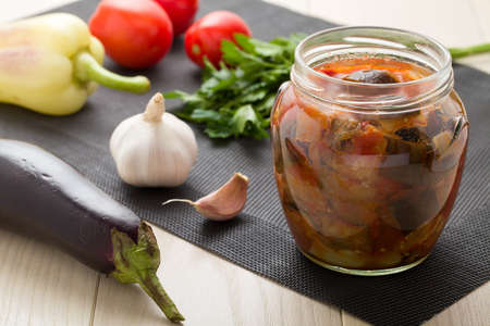 eggplants: Cooked stewed eggplants in jar for canning with raw vegetables   garlic, parsley, tomatoes, pepper on wooden table