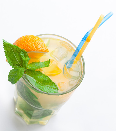 Glass of fresh made non-alcoholic drink citrus lemonade with ice cubes, mint , orange segment and straws. Top view on white background photo