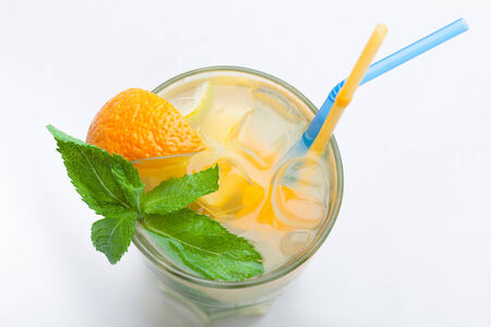 nonalcoholic: Glass of fresh made non-alcoholic drink citrus lemonade with ice cubes, mint , orange segment and straws. Top view on white background