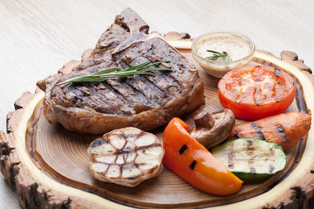 t bone: Portion of BBQ t-bone steak  served  on wooden board with  rosemary, mustard sauce  and grilled vegetables