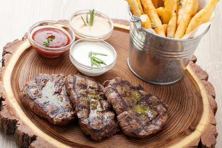 mignon: Portion of BBQ beef filet mignon steak  served  on wooden board with  ketchup, mustard and cream sauces, fried potatoes in aluminium bucket Stock Photo
