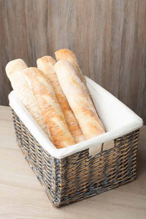 Stack of traditional fresh-baked French bread loafs baguette served in woven basket on wooden background photo