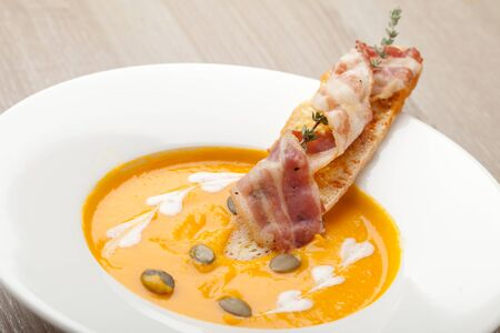 aftertaste: Pumpkin cream soup puree with ginger smack,  served in white plate , baked bread slice, bacon, seeds and  thyme