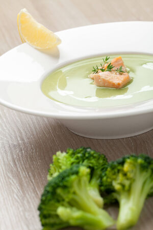 Green cabbage broccoli cream soup puree in white plate  served with  filleted salmon pieces , lemon and  theme Stock Photo