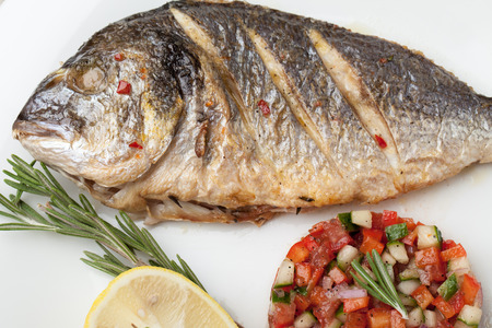 gilthead: Gourmet Mediterranean seafood dish. Grilled fish gilthead served with vegetable salsa, lemon, rosemary on white plate top view