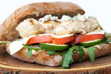 sandwich de pollo: Saludable hamburguesa sándwich de trigo con barbacoa parrilla filete de pollo, queso, tomate, ensalada de rúcula, pepino, patata frita y salsa de mostaza sirve para comer en la tabla de madera