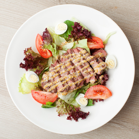 Fresh salad mix with grilled beef, meat cherry tomatoes , boiled quail eggs and  mustard  sauce served on table in white plate Stock Photo
