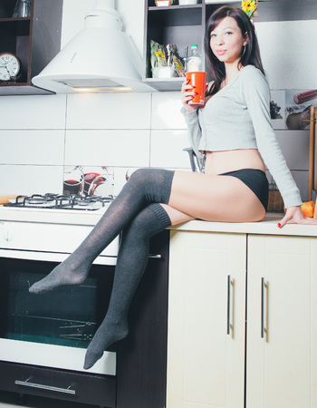 Hot brunette on the kitchen. Sexy young woman cooking.