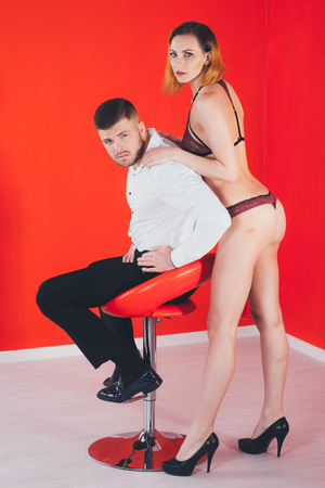Young woman in lingerie seducing a man in a chair