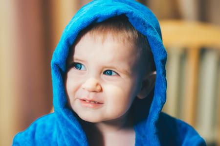 A little blue-eyed baby boy in a deep blue bathrobe Stock Photo