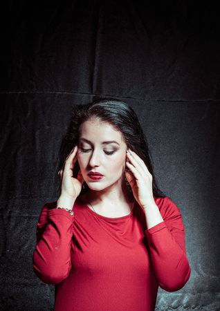 A portrait of a young pretty brunette on a dark background Banco de Imagens