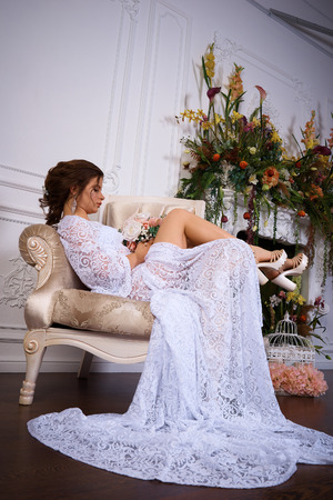 A portrait of a young pretty brunette in a long white dress Stock Photo
